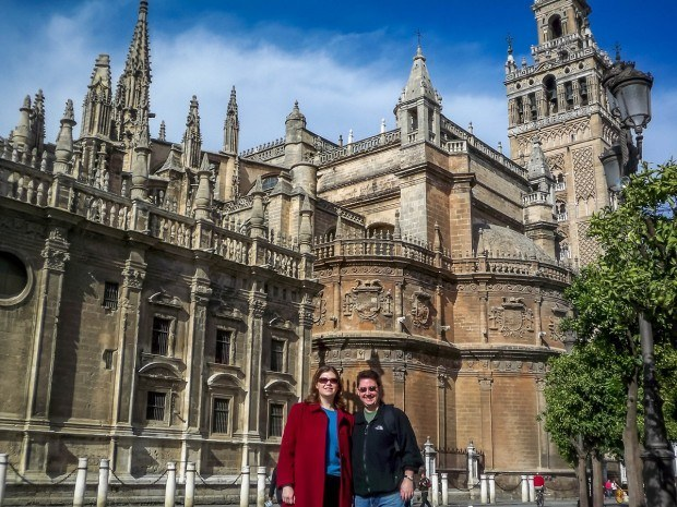 The Travel Addicts in front of the Seville Cathedral.