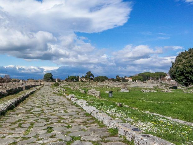 The ancient Roman cobblestone road inside Paestum Italy.  Walking the cobblestone street, Via Sacra, is like traveling back in time to ancient Italy.