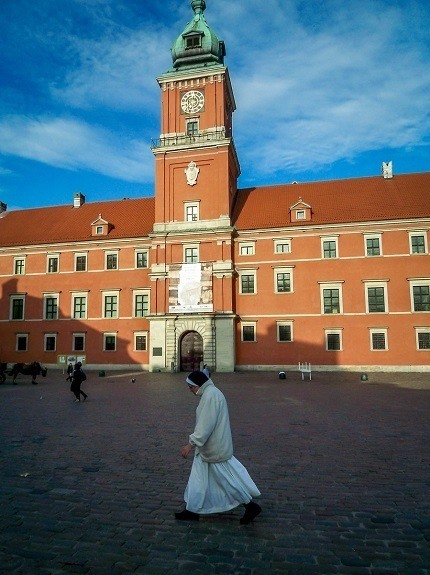 A nun walking in front of the Royal Castle in Warsaw, Poland.