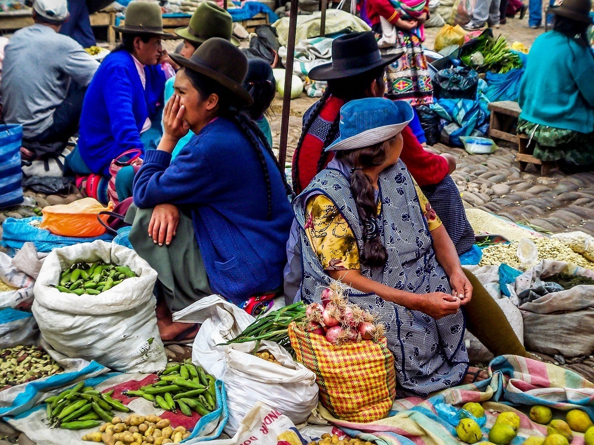 Vendors selling vegetable at the Pisac market in the Sacred Valley of Peru