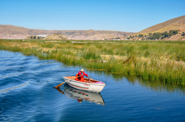 Peruvian woman rowing to the Uros islands in Lake Titicaca