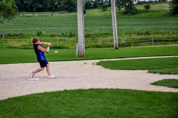 Boy hitting baseball on the diamond at the Field of Dreams location in Dyersville, Iowa.
