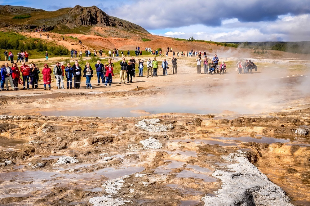 Group of people standing near the geyser
