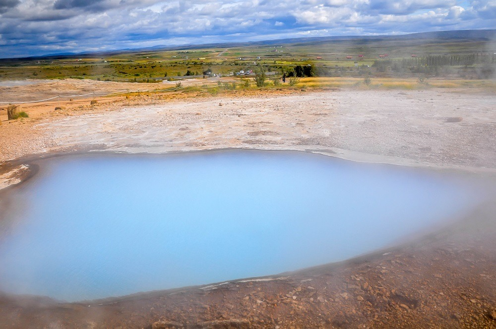 Bright blue geothermal pool near geysir
