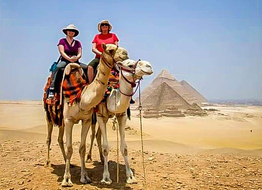 Trips to Egypt Pyramids:  Camel riders and the Great Pyramid Giza