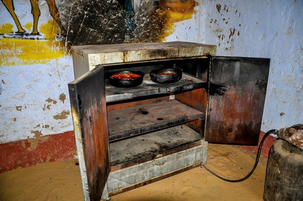 Dishes in oven on a dirt floor