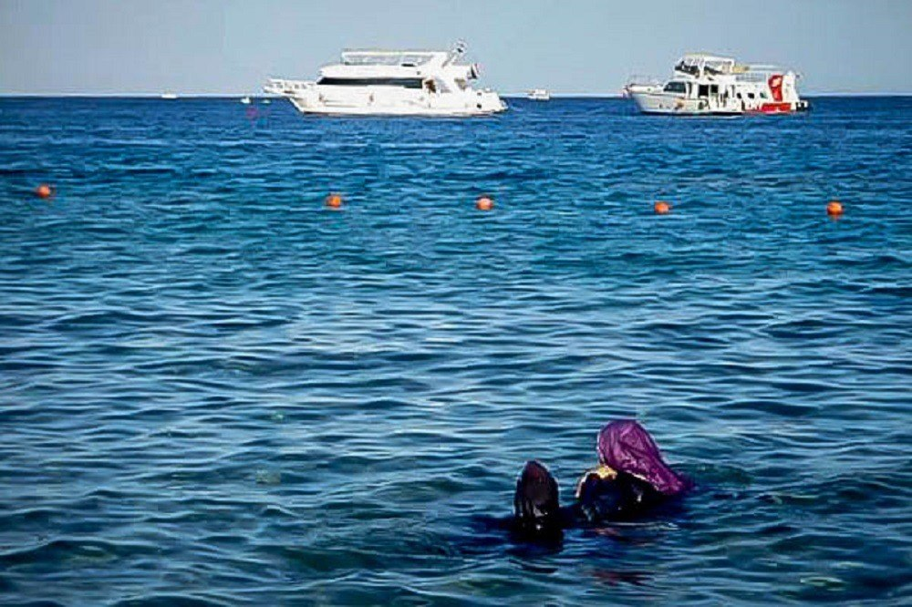 Women watching the scuba and dive boats offshore in Sharm el Sheikh Egypt
