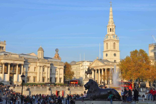 Trafalgar Square with lion sculpture and lots of people near sunset in London