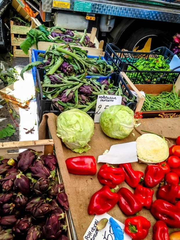 A table of peppers, lettuce, and artichokes for sale on Siena market day