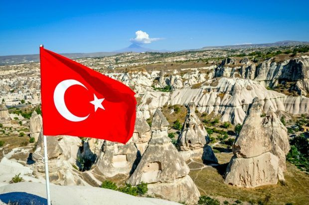 The Turkish flag in Cappadocia with fairy chimneys.