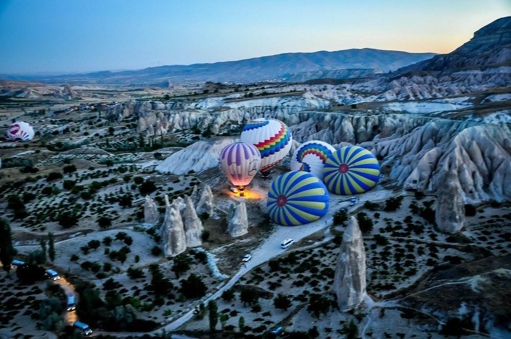 Hot air balloons inflating amid rock formations