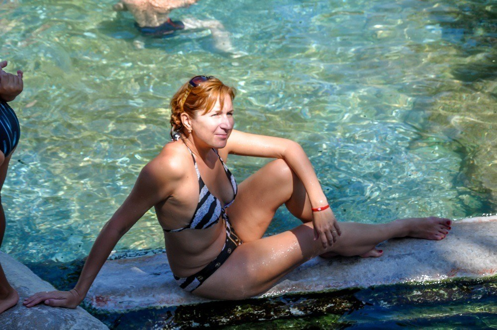 Woman posing for photos in the antique pool of the Pamukkale thermal pools