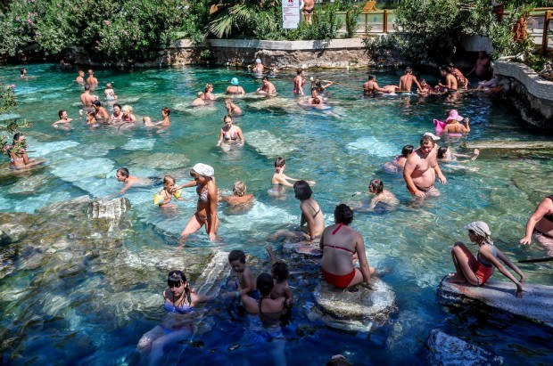 Visiting the Pamukkale Turkey Cleopatra's pool:  Visitors lounge in the Pamukkale hot springs antique pool.