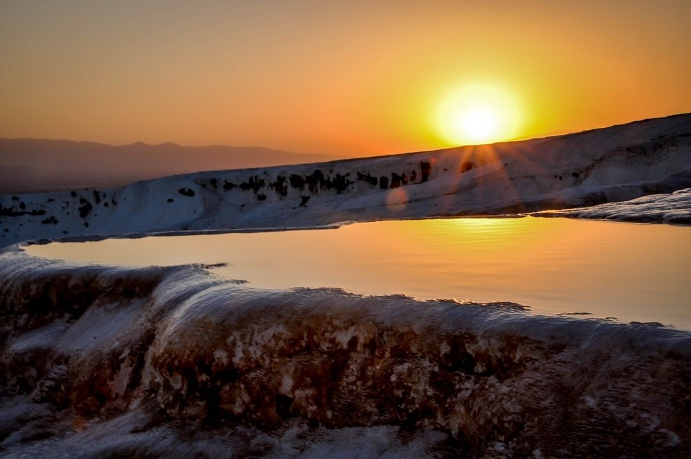 Sun setting over the travertine terraces in Pamukkale, Turkey.