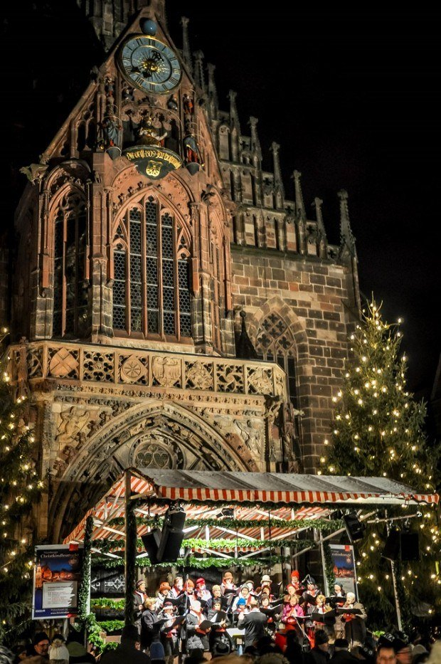 Frauenkirche church lit up at night in Nuremberg Germany, with a Christmas choir