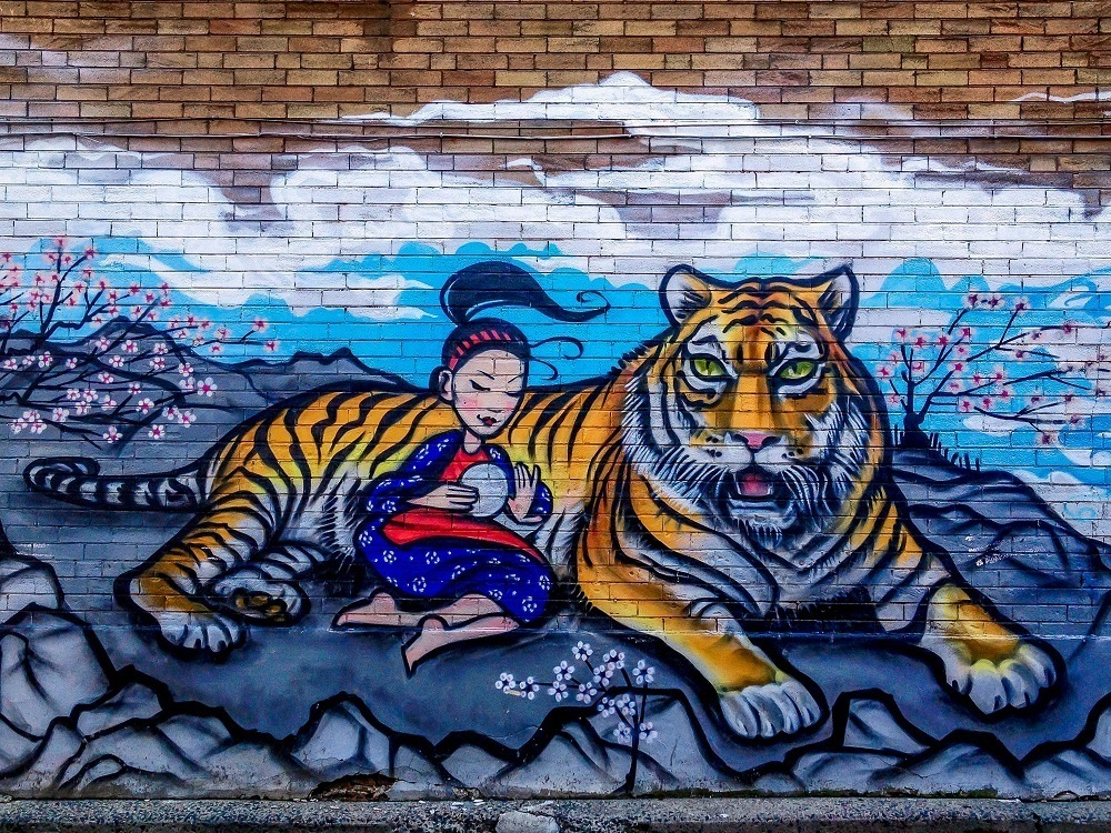Street art in Chinatown of a girl and a tiger