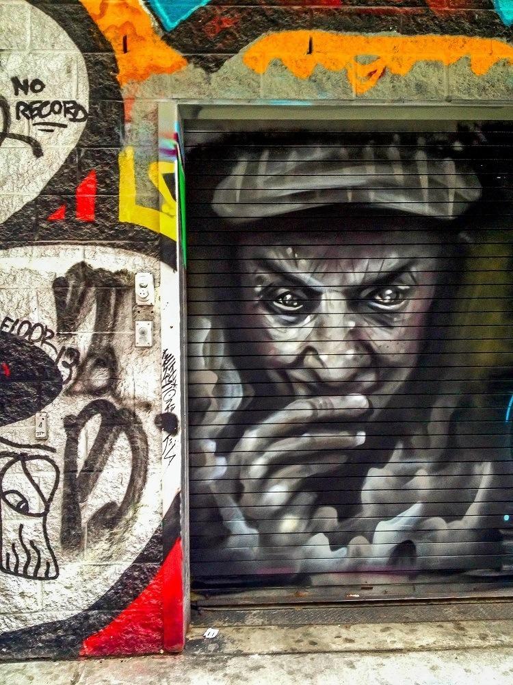 Street art featuring sneaky man in Graffiti Alley Toronto