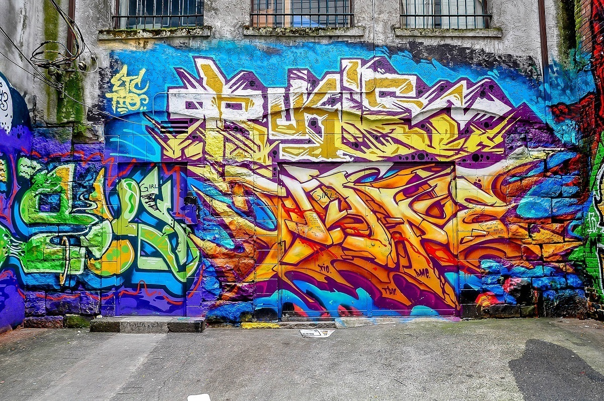 Multi-colored graffiti tag on brick wall