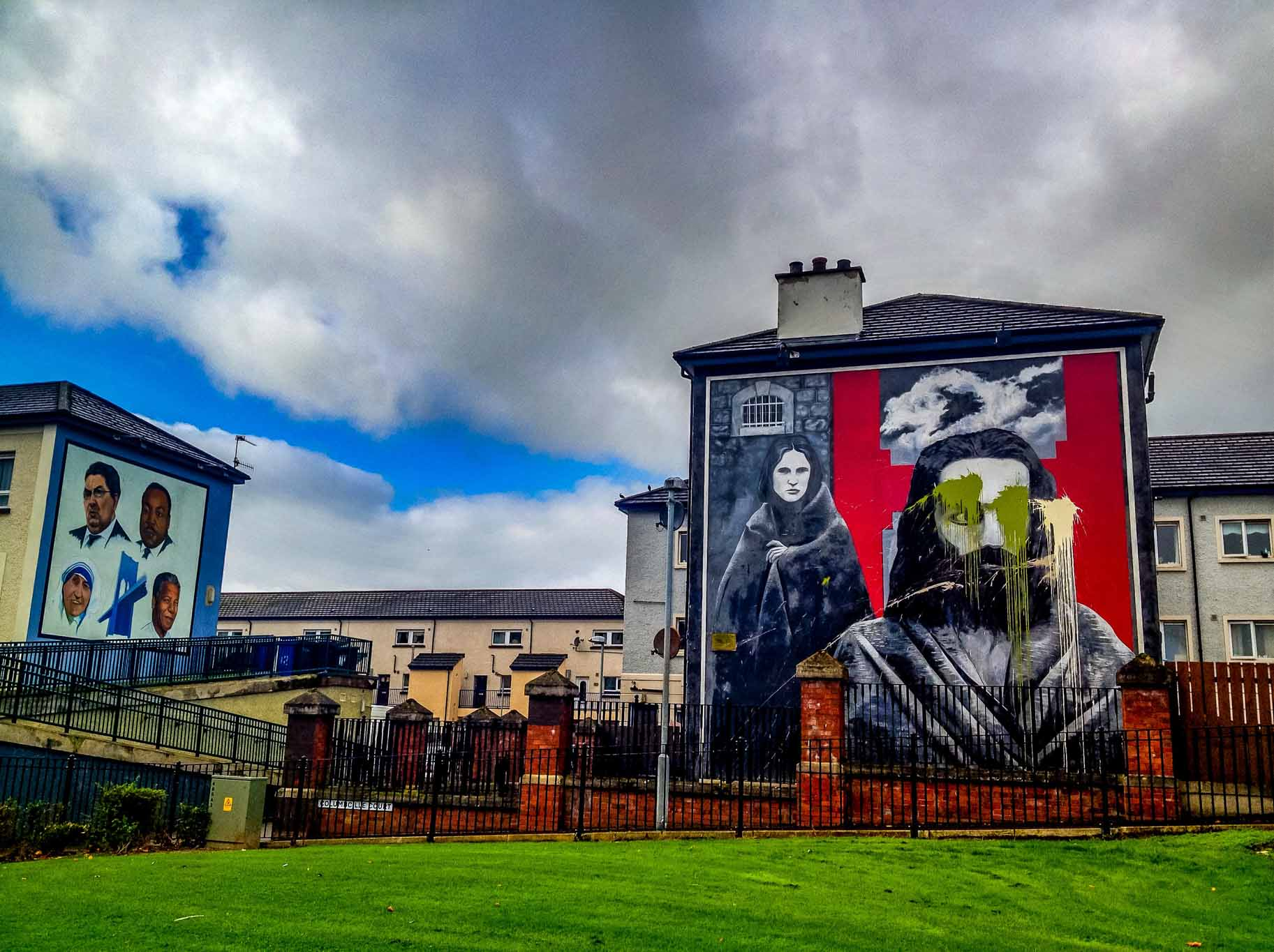 Two of the IRA murals in Derry -- The Hungers Strikers mural with vandalism and the John Hume mural