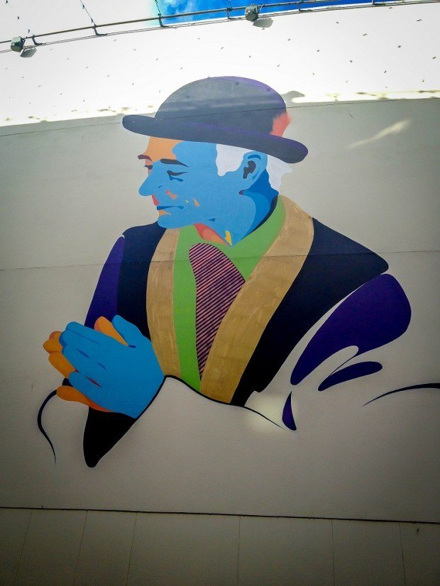 Multi-colored street art of man in a bowler hat