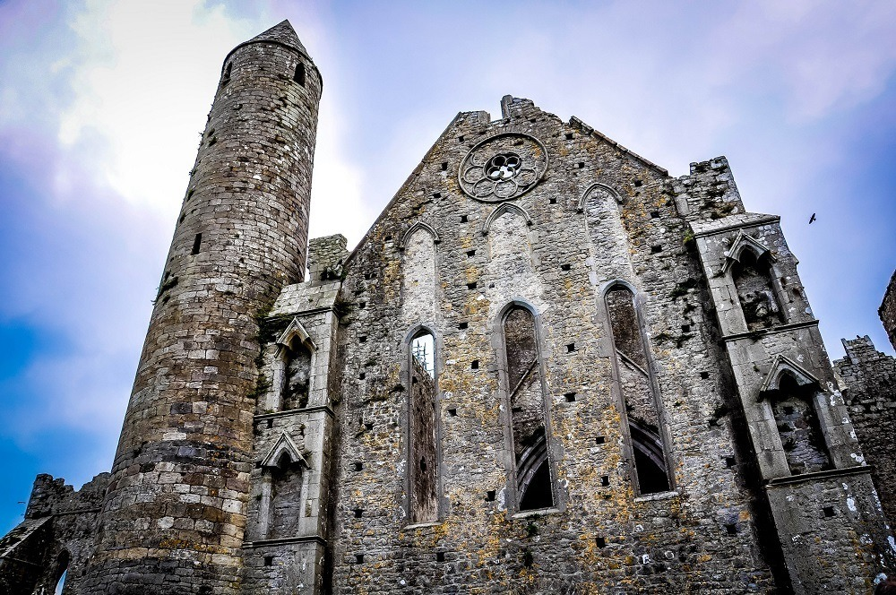Stone tower and chapel ruins at Rock of Cashel on an Ireland itinerary 10 days