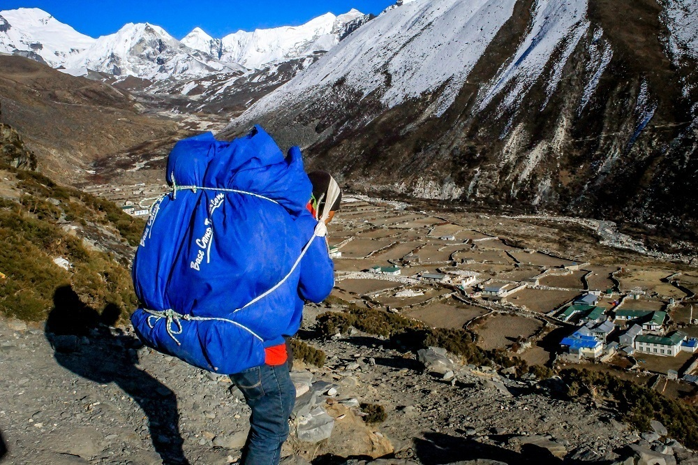 A Sherpa porter in Nepal carrying gear during a Trek