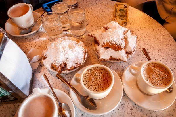 Table with beignets and coffee. Probably the most famous food in the city, beignets at Cafe Du Monde is one of the New Orleans highlights