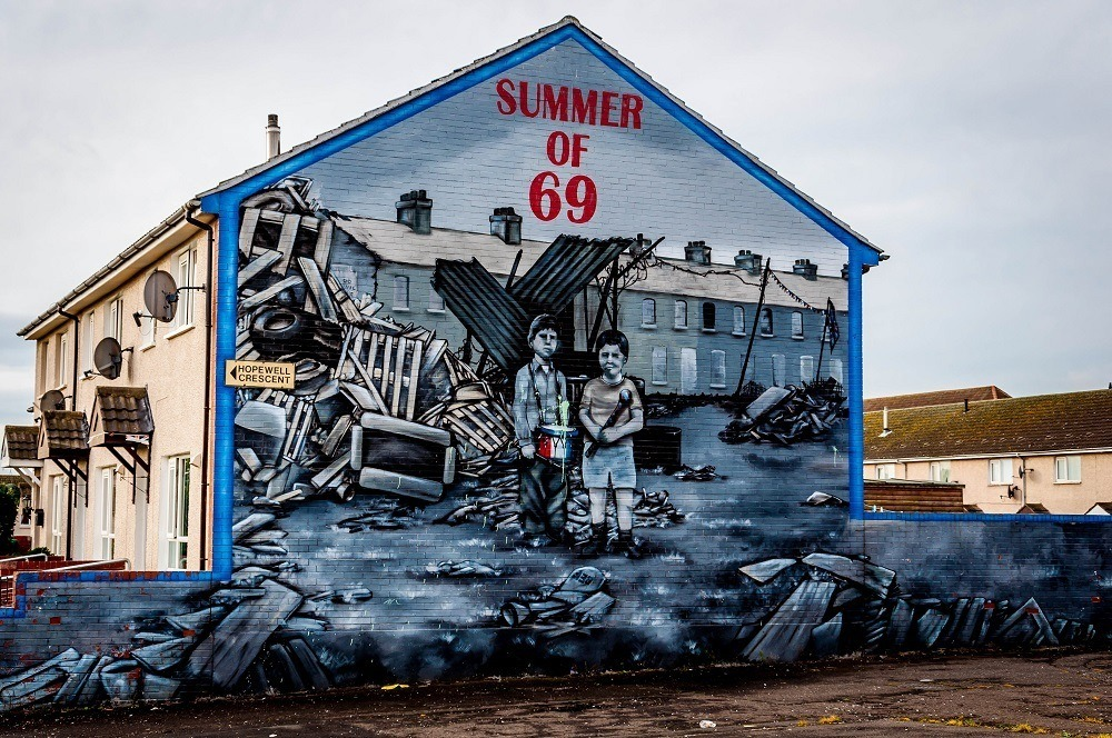 "Street art mural with the label ""Summer of 69"" showing young boys among ruins"