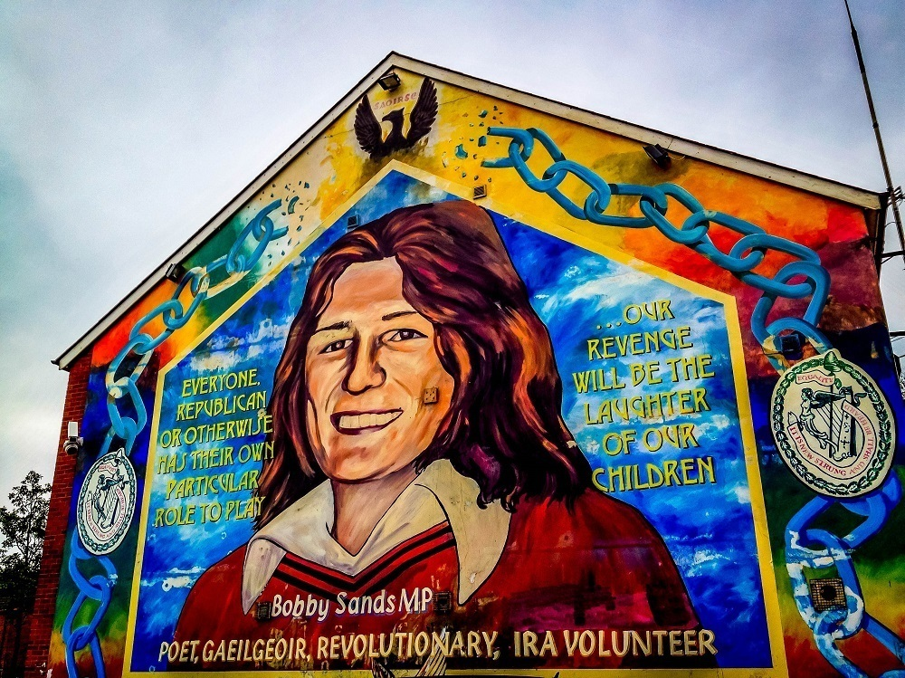 Colorful mural honoring Bobby Sands shows man and broken chains