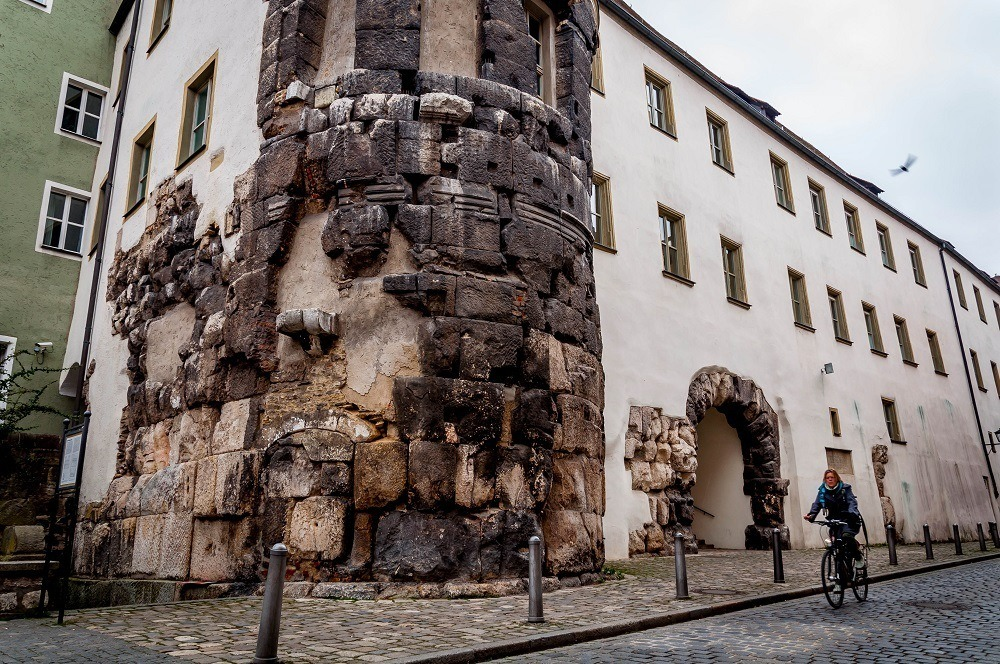 Bicyclist riding by the Porta Praetoria from the Roman military outpost Castra Regina in Regensburg