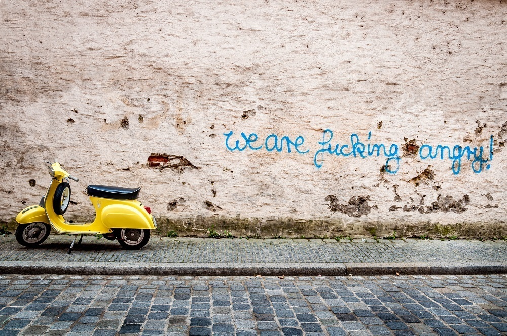 Graffiti on city wall saying We Are Fucking Angry! next to a yellow moped