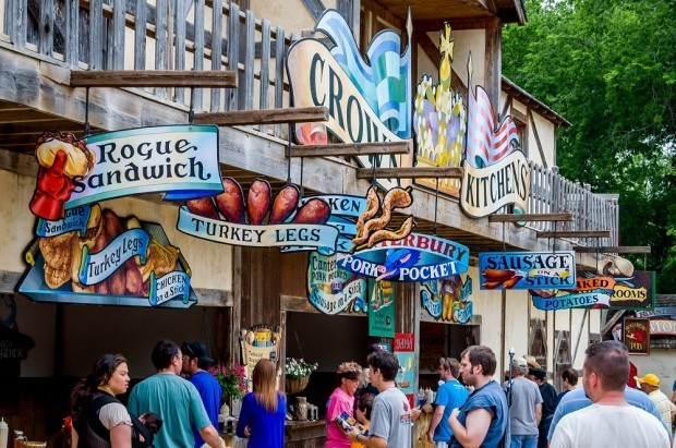 Multicolored signs advertising Renaissance faire food at Scarborough Fair Texas