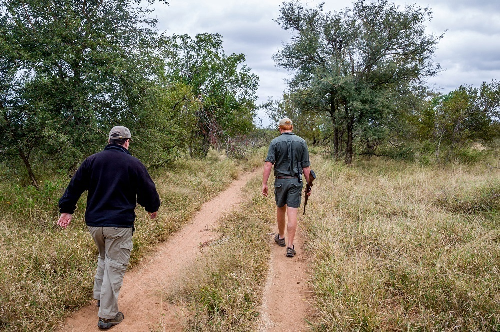 Lance walking with guide at Africa on Foot safari camp
