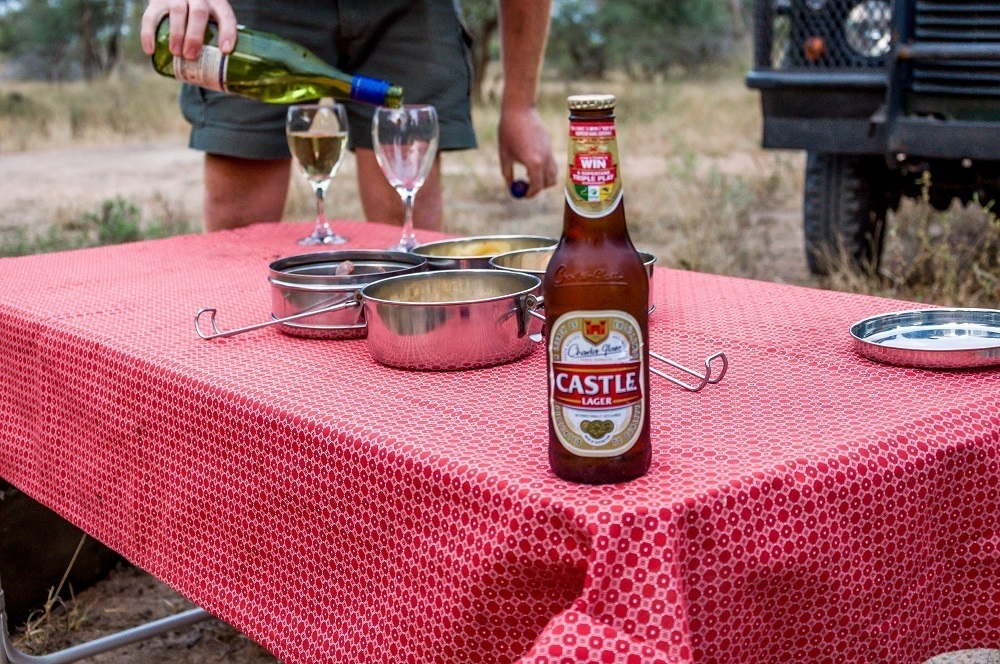 Safari sundowner with red tablecloth, beer and wine