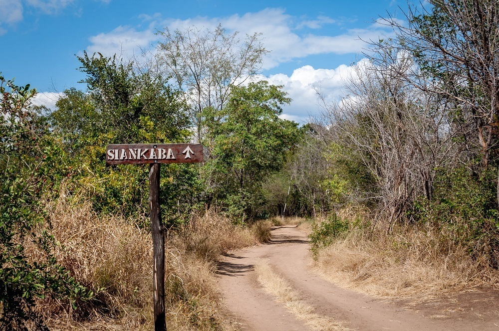 Sign on dirt road point to Siankaba