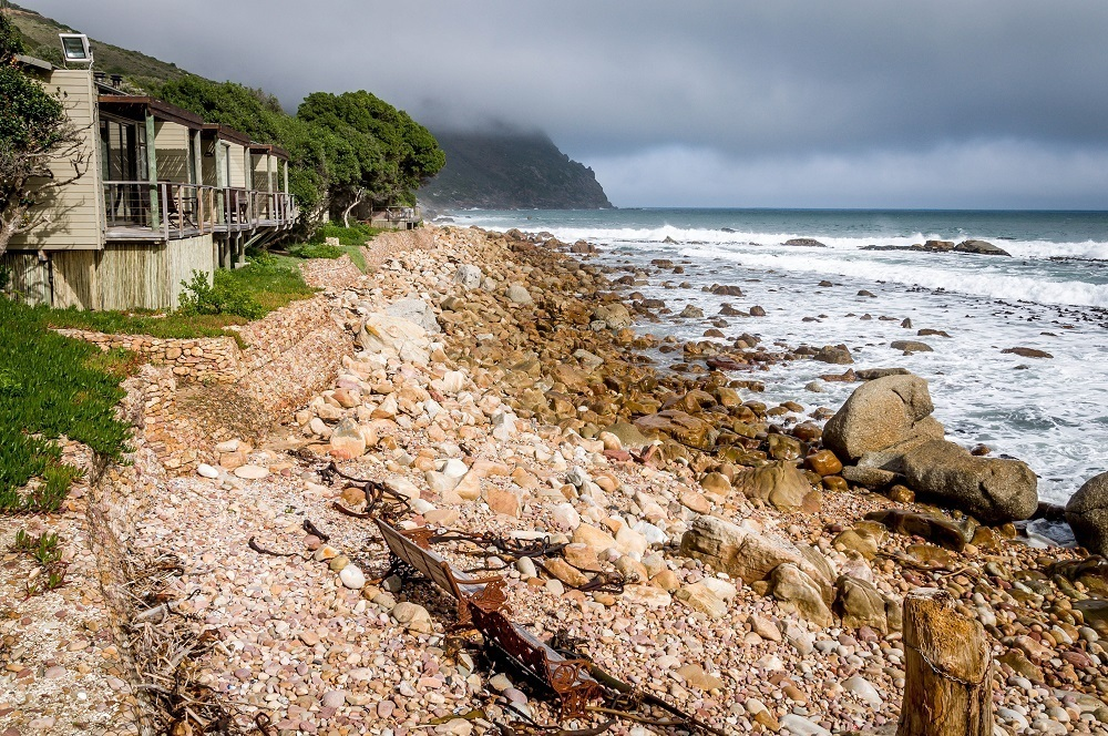The Tintswalo Atlantic blends into the vegetation just above the rocky coastline of Hout Bay Cape Town, South Africa.