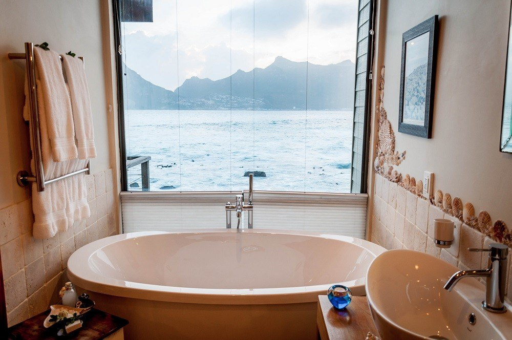 The large soaker bathtub looks right out on Hout Bay and Sentinel Peak.