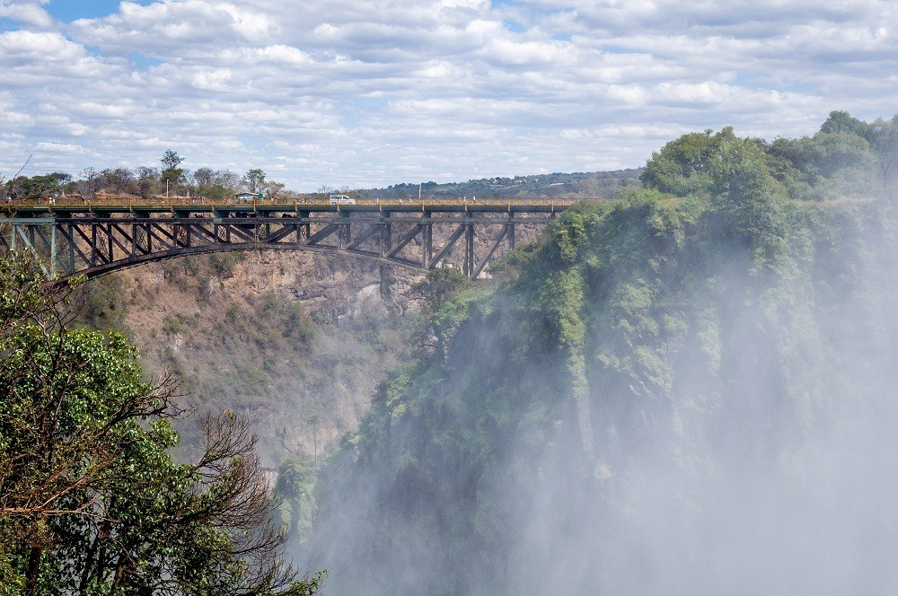 The mist at Victoria Falls can partially obscure the view of the Victoria Falls Bridge below.
