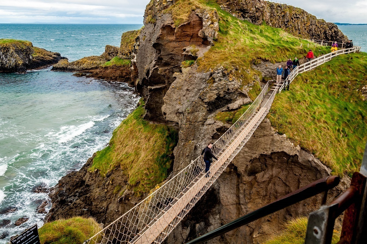 People crossing the Carrick-a-Rede rope bridge above the ocean in Northern Ireland