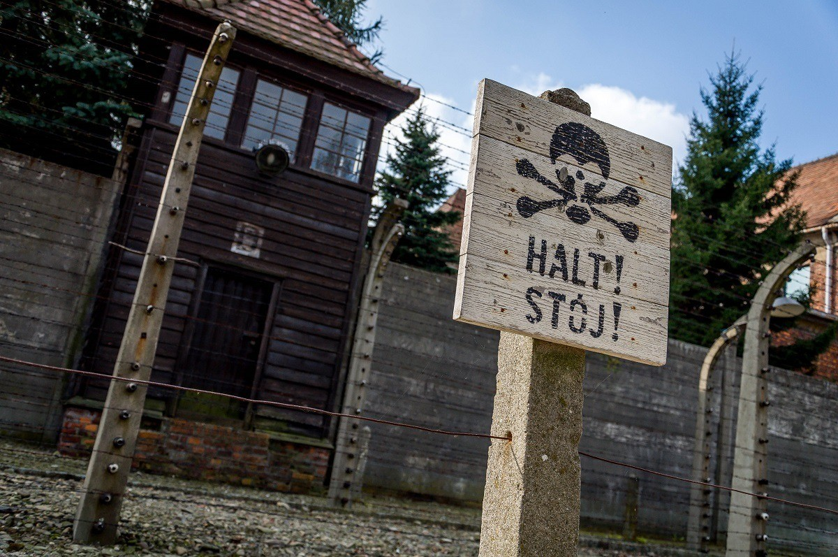 A sign warning prisoners to stop before the electrified fence inside the Auschwitz concentration camp