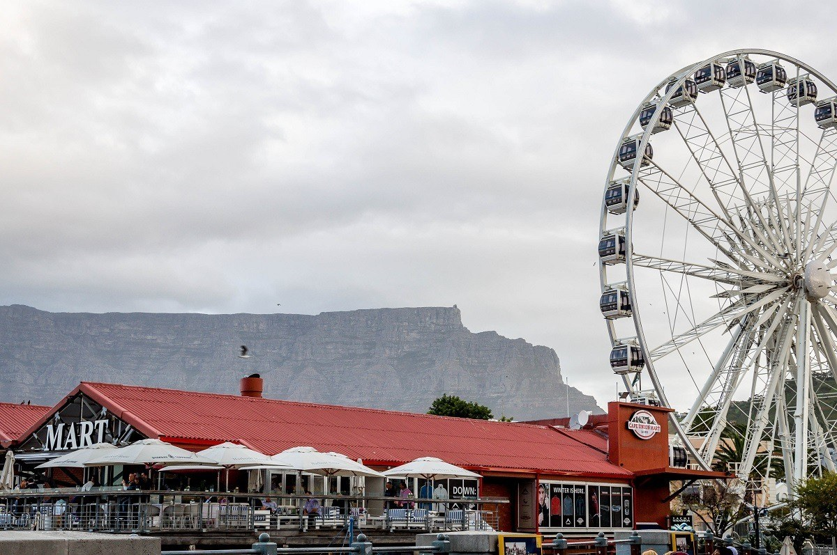 The Cape Wheel at the V&A Waterfront, with Table Mountain in the background.  The V&A Waterfront is one of the top Cape Town attractions and is actually the most visited site in all of Africa.