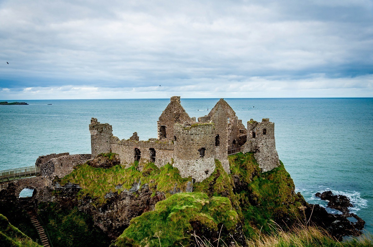 Ruins of the Dunluce Castle on the Antrim Coast Road in Northern Ireland. This is the castle near Giant's Causeway Northern Ireland. Visiting Dunluce Castle with Mermaids Cave is one of the top things to do in Antrim.  And while many visitors go to the castle, many overlook the Dunluce Castle Mermaid's Cave beneath (there is also a Giant's Causeway Cave too).  If you visit Giants Causeway Ireland, be sure to come here too!