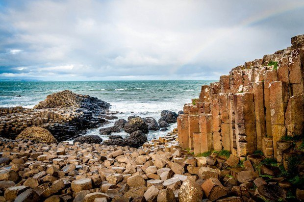 A rainbow over the iconic basalt columns of The Giant's Causeway in Antrim, Northern Ireland.