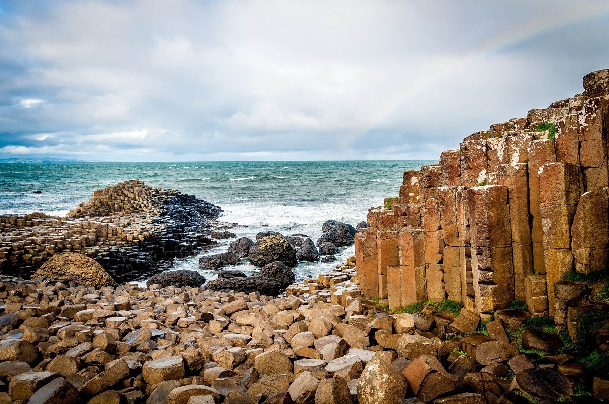 Rainbow over basalt columns of Giant's Causeway and the ocean