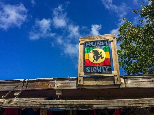 The Rush Slowly sign at the Reggae Beach Bar St Kitts beach.