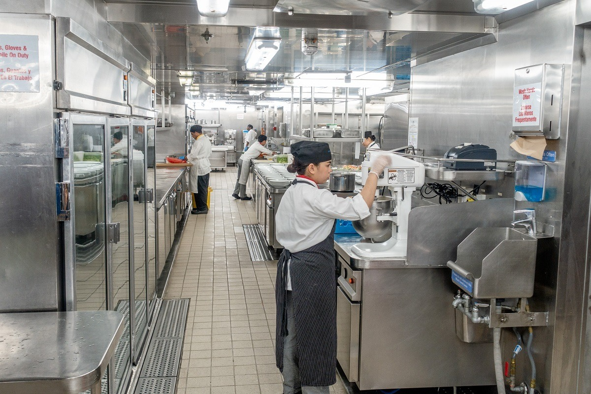 Kitchen employee using a stand mixer in the ship's galley