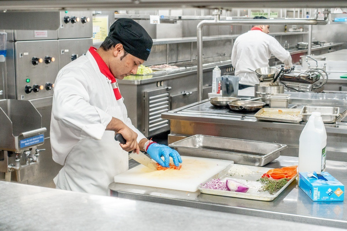 An employee cutting food on a Celebrity Summit galley tour