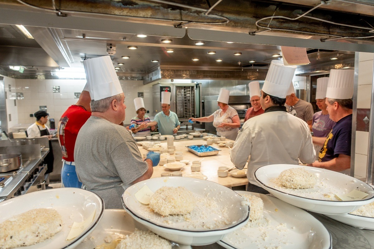 People wearing chefs hats in a cooking class on the Celebrity Summit