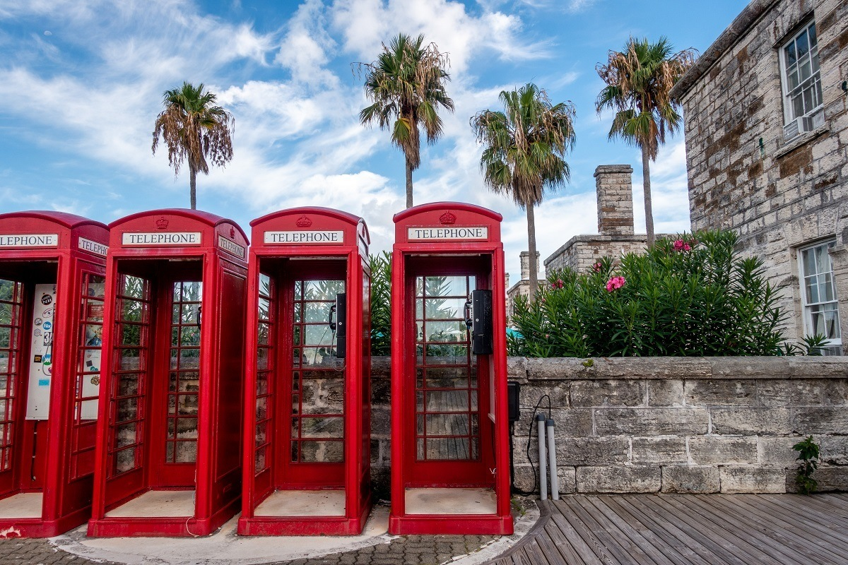 Red British-style phone booths with palm trees in Bermuda