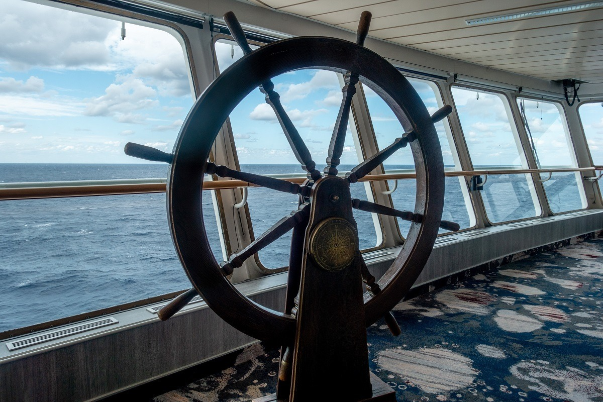 Steering wheel on the ship's bridge overlooking the ocean